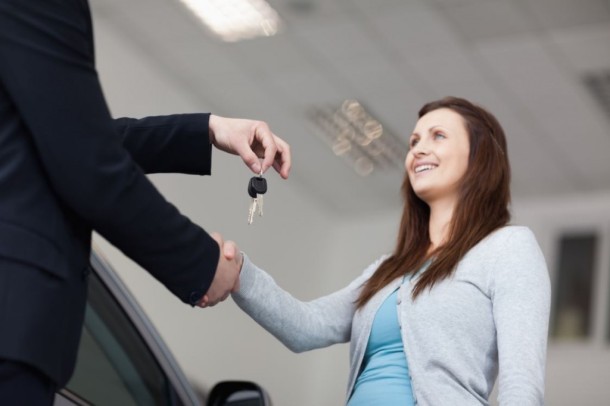 smiling car customer shaking hands with keys